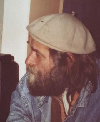 Raimund Samuelson - Art Brut Künstler aus Gronau. Ein älterer Mann mit heller Baskenmütze, schulterlangen Haaren und einem Vollbart in Profilansicht.